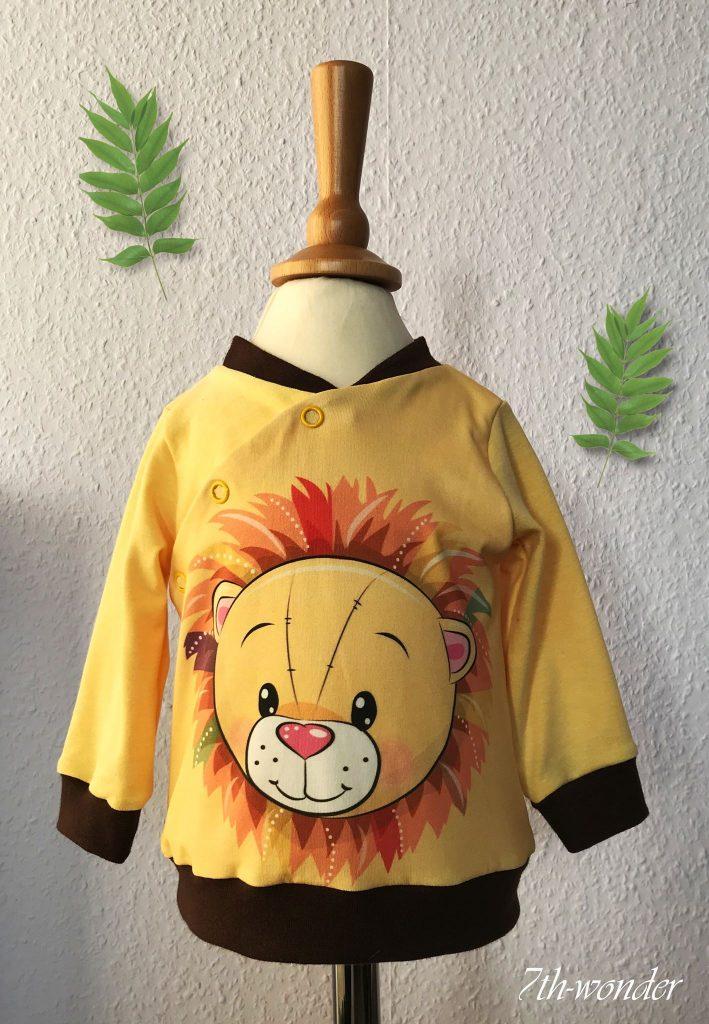 Gelber Pullover mit Löwenkopf